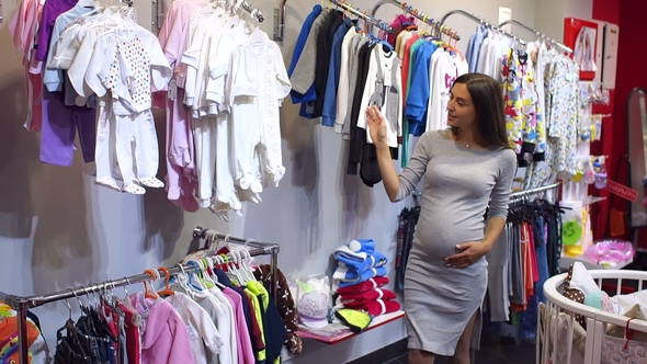 Pregnant Woman Choosing Baby Clothing In Baby Shop By Tytarenko