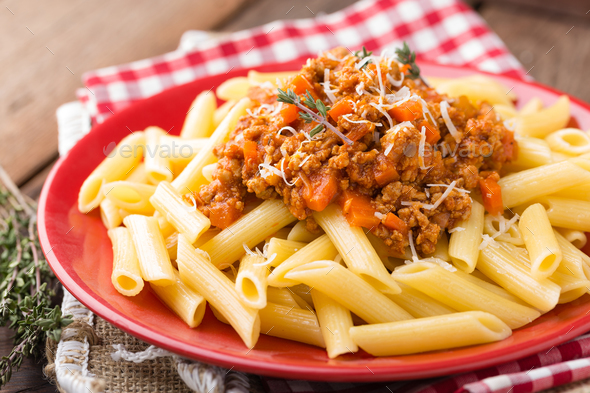 Pasta bolognese. Pasta served with a sauce of ground beef meat, tomato, onion, carrot and thyme - Stock Photo - Images