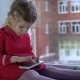 A Little Sweet Girl in a Pink Dress Sits on the Windowsill and Uses a Smartphone - VideoHive Item for Sale