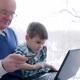 Internet Shopping, Old Man with Plastic Card and Child Make Online Purchases Via Laptop at Home - VideoHive Item for Sale
