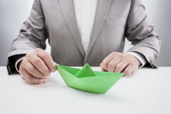 Businessman with a green paper boat - Stock Photo - Images