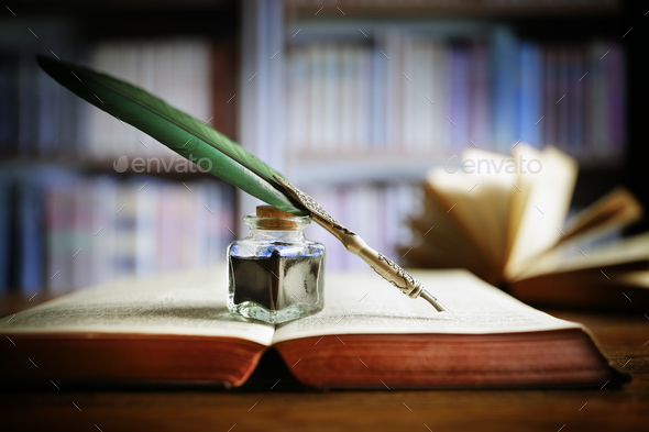 Quill pen on an old book in a library - Stock Photo - Images