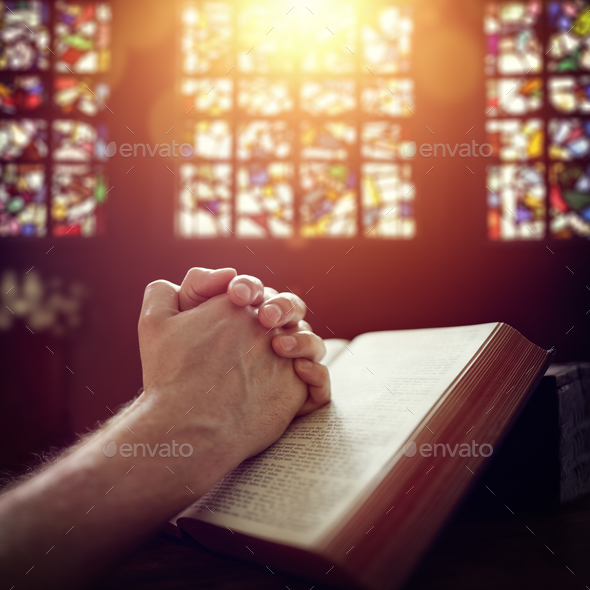 Praying hands on a Holy Bible - Stock Photo - Images