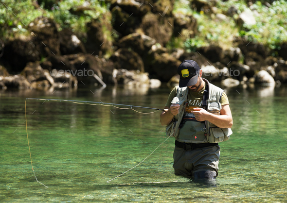 Fly fisherman flyfishing in river - Stock Photo - Images