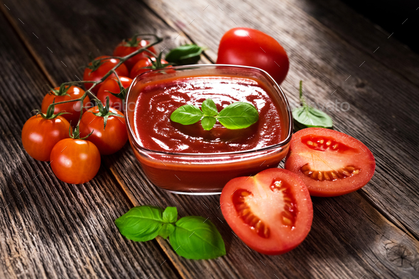 Tomato sauce and fresh tomatos on rustic background - Stock Photo - Images