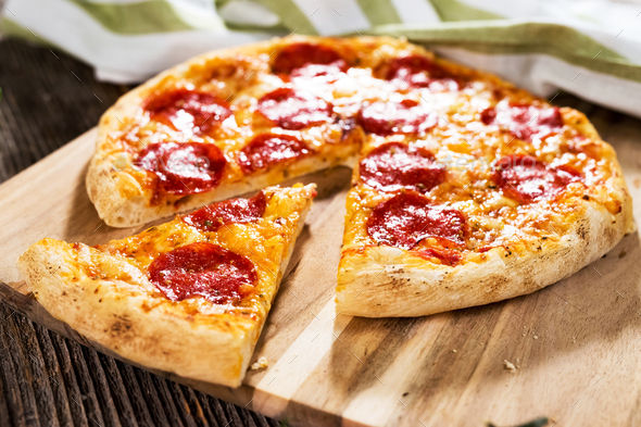 Pepperoni pizza on rustic background - Stock Photo - Images