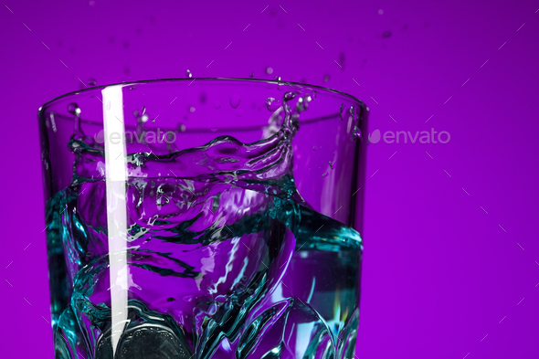 The water splashing in glass on lilac background - Stock Photo - Images