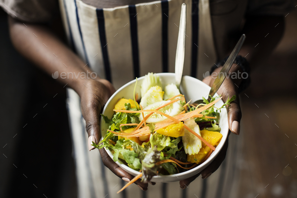 Black woman holding the salad bowl - Stock Photo - Images