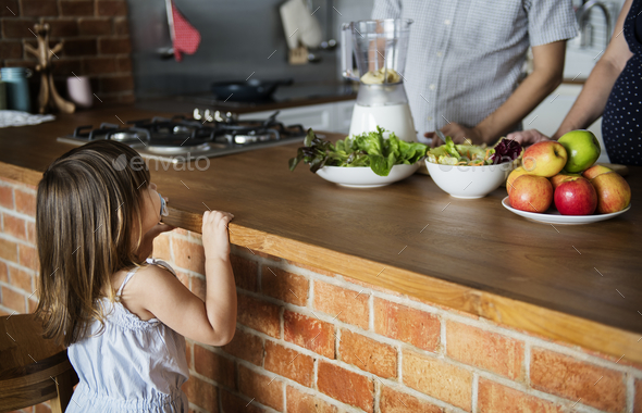 Family making smoothie in the kitchen - Stock Photo - Images