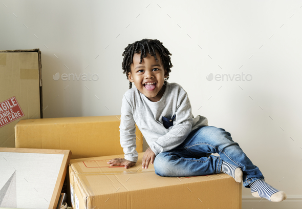 Young cheerful black boy moving to new house - Stock Photo - Images