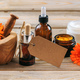 Calendula aromatherapy. Essential oil and cosmetics, blank tag, banner. Wooden table background - PhotoDune Item for Sale