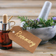 Rosemary essential oil and fresh blooming twig in a mortar, wooden table, tag with text rosemary - PhotoDune Item for Sale