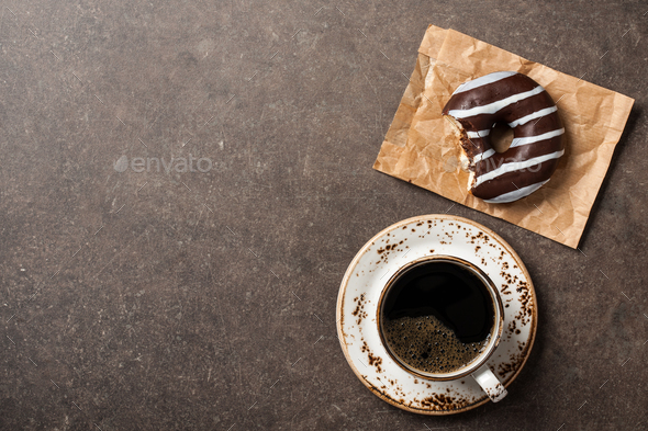 Chocolate donut and cup of coffee on table - Stock Photo - Images