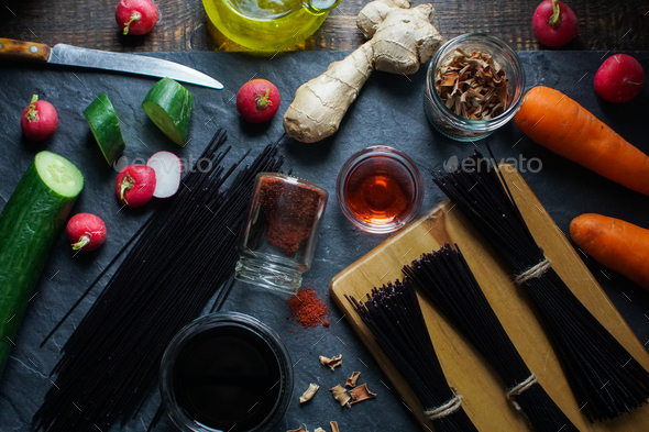 Black rice vermicelli, vinegar and vegetables on a black slate view from above. Asian cuisine - Stock Photo - Images
