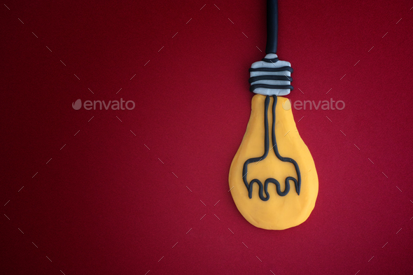 Light bulb made out of play clay on red background - Stock Photo - Images