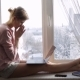 Sad and Upset Woman Using Her Laptop Sitting on Window Sill - VideoHive Item for Sale