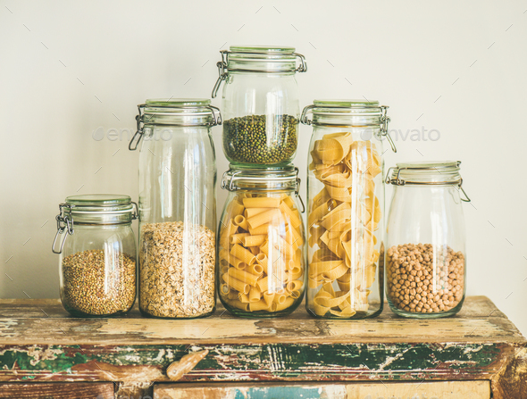 Uncooked cereals, grains, beans and pasta on rustic wooden table - Stock Photo - Images