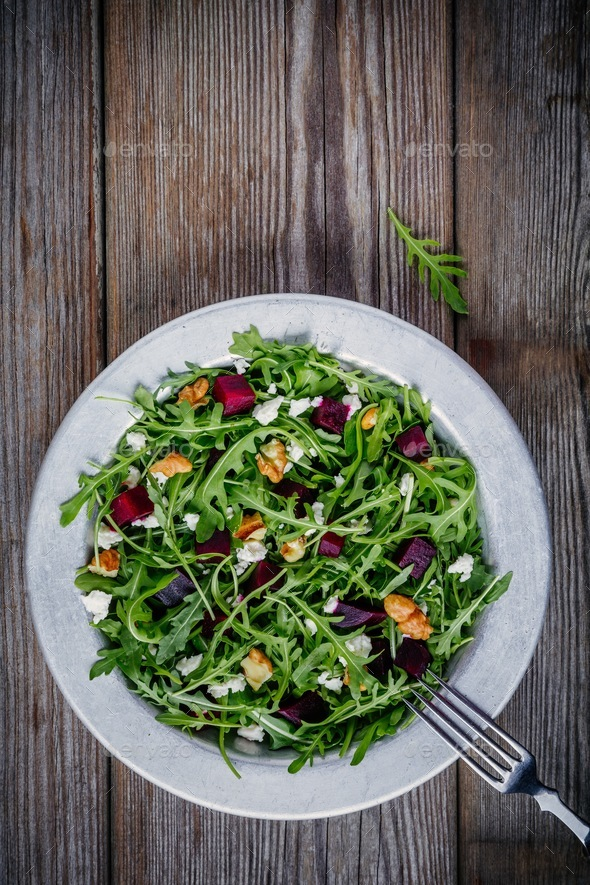 Fresh green salad with arugula, beets, walnuts and feta cheese - Stock Photo - Images