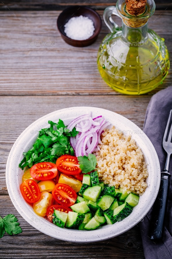 Healthy Quinoa Tabbouleh Salad bowl with fresh cucumbers, tomatoes and red onions - Stock Photo - Images