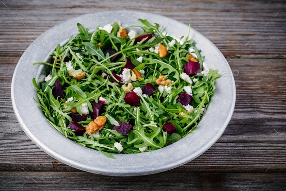 Fresh green salad with arugula, beets, walnuts and goat cheese - Stock Photo - Images