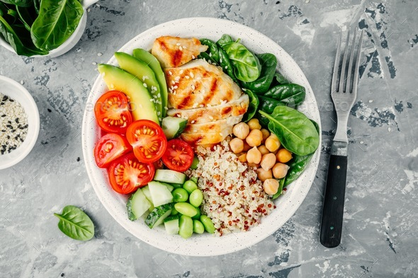 Buddha bowl with spinach, quinoa, chickpeas, grilled chicken, avocado, tomatoes, cucumbers - Stock Photo - Images