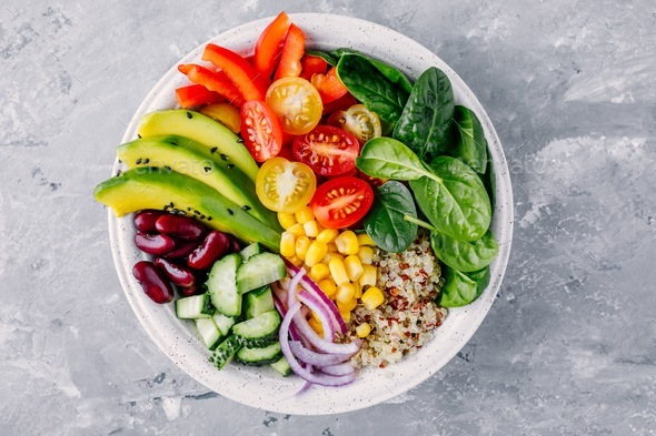 Healthy vegan lunch Buddha bowl. Avocado, quinoa, tomato, red beans, spinach salad. - Stock Photo - Images