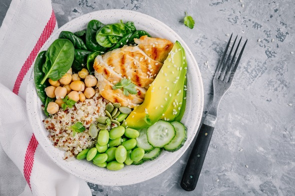 Buddha bowl with spinach, quinoa, chickpeas, grilled chicken, avocado, edamame beans, cucumbers - Stock Photo - Images