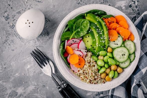 Vegan Buddha bowl with spinach, quinoa, chickpeas, avocado, edamame, cucumbers, carrots and sesame - Stock Photo - Images