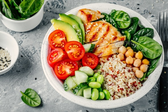 Buddha bowl with spinach salad, quinoa, chickpeas, grilled chicken, avocado, tomatoes, cucumbers - Stock Photo - Images