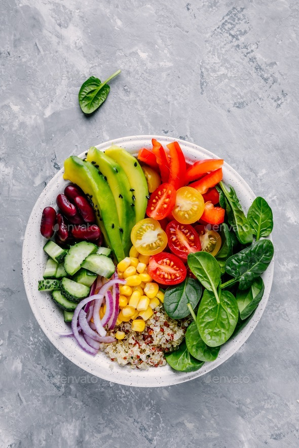 Buddha bowl. Avocado, quinoa, tomato, cucumber, red beans, spinach, red onion and red paprika - Stock Photo - Images