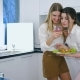 Happy Girlfriends, Mobile Phone in Hands of Young Women in Kitchen During Brunch on Day Off - VideoHive Item for Sale