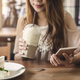 Young woman using smart phone and eating cake in cafe - PhotoDune Item for Sale
