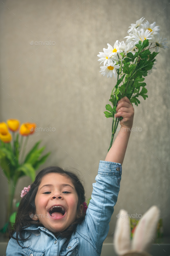 Excited baby girl with flowers - Stock Photo - Images