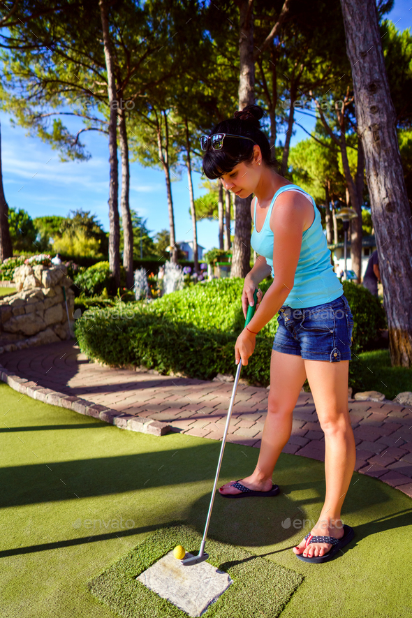Mini Golf - Woman playing Golf on green grass at sunset - Stock Photo - Images