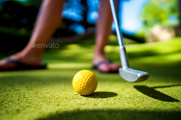 Mini Golf yellow ball with a bat at sunset - Stock Photo - Images