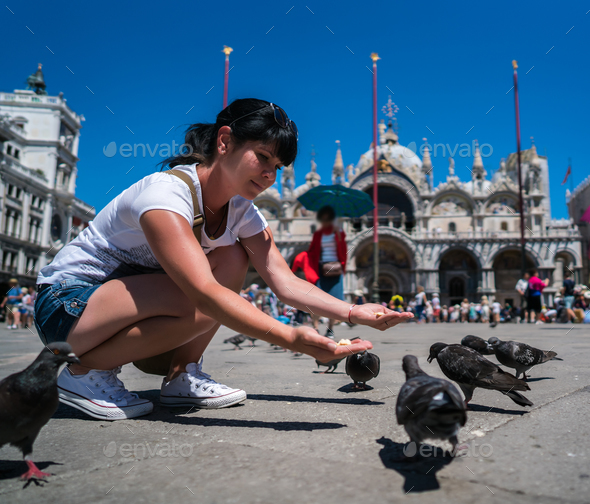 Woman tourist feeding pigeons in the square - St. Marks Square - - Stock Photo - Images
