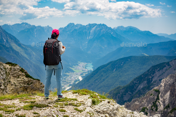 Hiker woman standing up achieving the top Dolomites Alps. - Stock Photo - Images