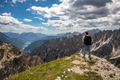 Hiker woman standing up achieving the top Dolomites Alps. - PhotoDune Item for Sale