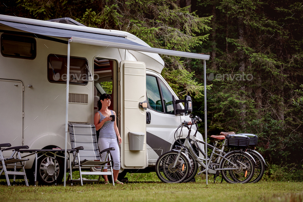 Woman is standing with a mug of coffee near the camper RV. - Stock Photo - Images