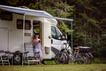 Woman is standing with a mug of coffee near the camper RV. - PhotoDune Item for Sale