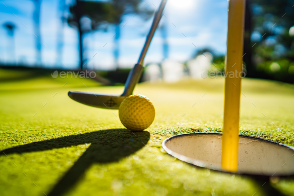 Mini Golf yellow ball with a bat near the hole at sunset - Stock Photo - Images