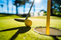 Mini Golf yellow ball with a bat near the hole at sunset - PhotoDune Item for Sale