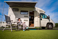 Woman resting near motorhomes in nature. Family vacation travel, - PhotoDune Item for Sale