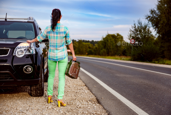 Woman with an empty tank of gas - Stock Photo - Images