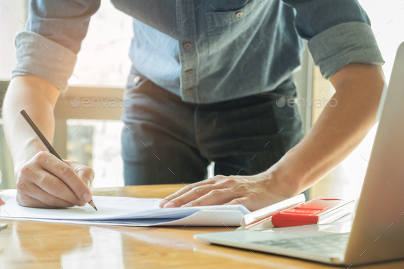 Architects are writing with home plan and laptop on the desk. - Stock Photo - Images
