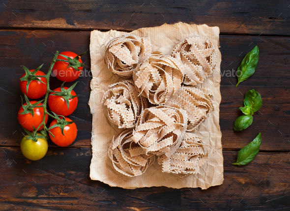 Whole wheat pasta tagliatelle, tomatoes and basil - Stock Photo - Images