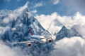 Airplane is flying over low clouds against mountains - PhotoDune Item for Sale