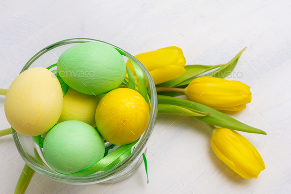Easter table centerpiece with yellow tulips  and painted eggs in - Stock Photo - Images
