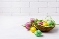 Easter green and yellow painted eggs in the nest and pink tulips - PhotoDune Item for Sale