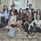 School Students Sit on the Steps of the School and Wave Their Hands - VideoHive Item for Sale